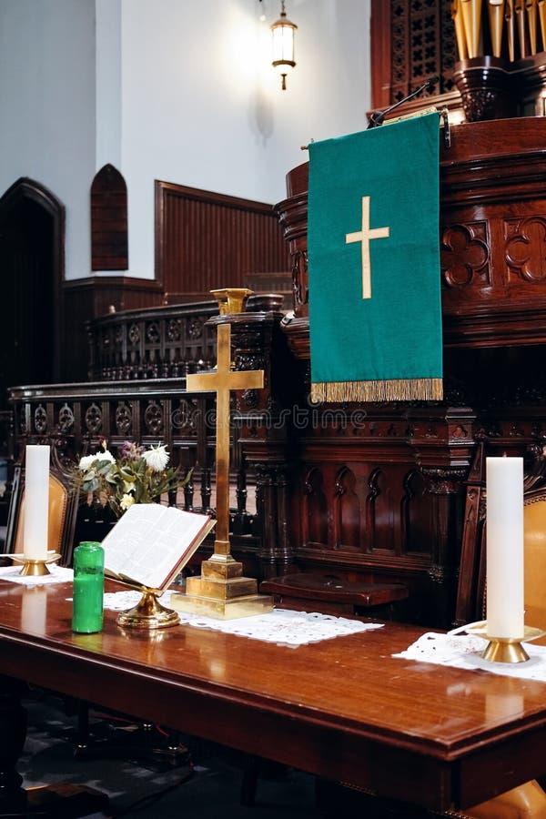 Interior de um altar da igreja com cruz, a Bíblia Sagrada e velas douradas nela imagem de stock royalty free