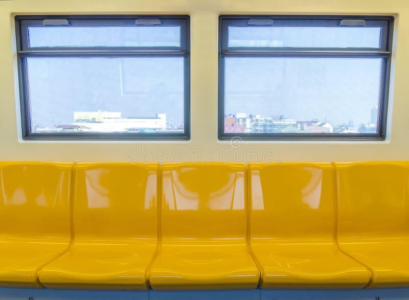 Interior de um carro de metro moderno, assento do amarelo do trem de céu foto de stock