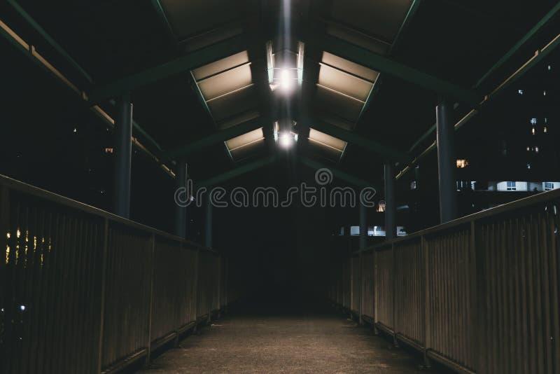 Interior de um celeiro de cavalo vazio com as gaiolas disparadas na baixa exposição fotografia de stock royalty free