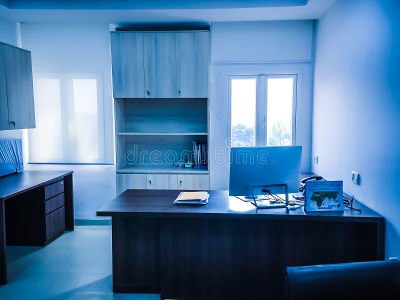 Interior de um escritório, do local de trabalho com janelas, de um computador e de tabelas imagem de stock