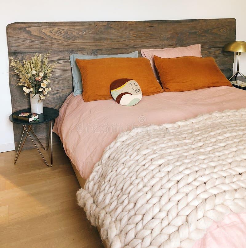 Interior de um quarto bonito com uma tampa de cama cor-de-rosa com a planta à esquerda imagens de stock