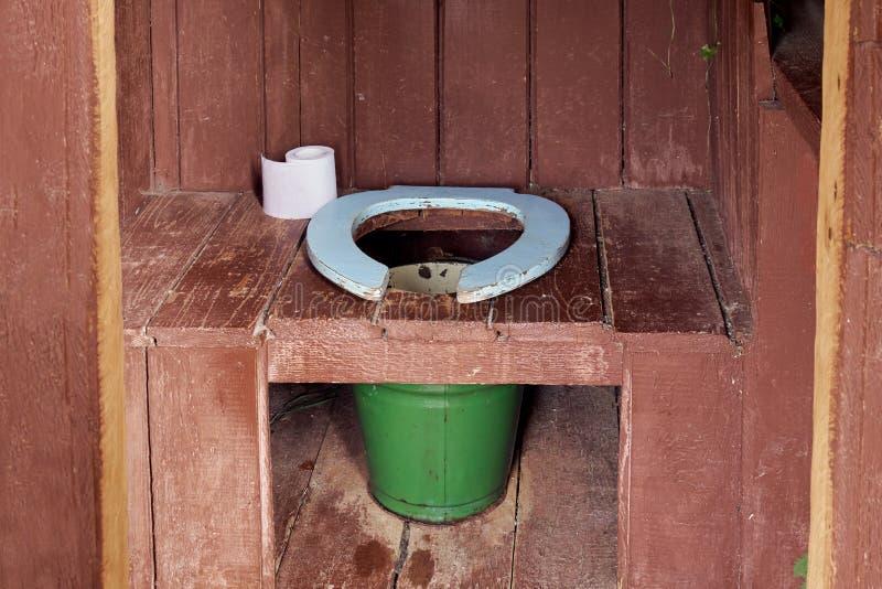 Interior de um toalete de madeira do país com uma cubeta do metal e um rolo de um papel imagens de stock