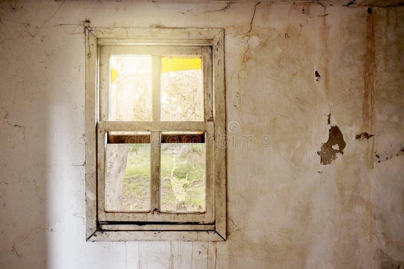 Interior de uma casa arruinada com a parede branca velha, suja e rachada e um quadro de janela quebrado com uma opinião verde do  foto de stock