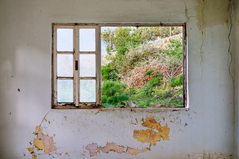 Interior de uma casa arruinada com a parede branca velha, suja e rachada e um quadro de janela quebrado fotografia de stock