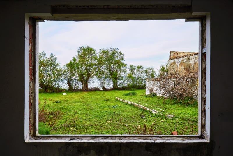 Interior de uma casa arruinada com um quadro de janela quebrado que vê um campo verde do prado foto de stock
