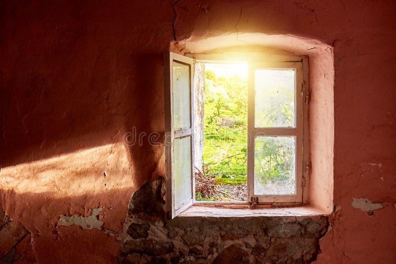 Interior de uma casa de campo velha arruinada com um claro - parede cor-de-rosa e um quadro de janela de madeira quebrado que vê  imagens de stock