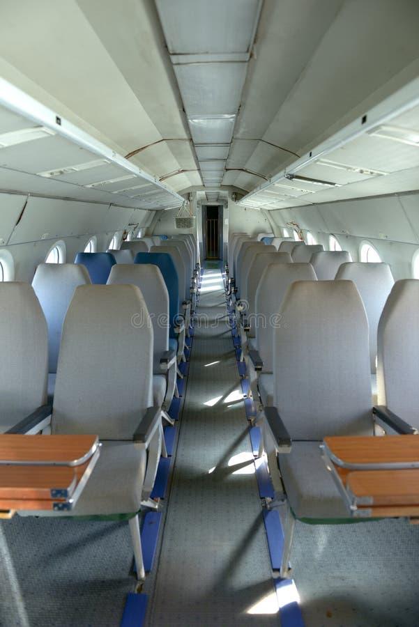 Interior de un aeroplano con muchos asientos foto de archivo