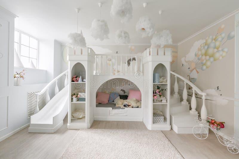 interior de un cuarto espacioso del ` s de los niños castillo decorativo con la cama dentro, la diapositiva del juego y las escal foto de archivo libre de regalías