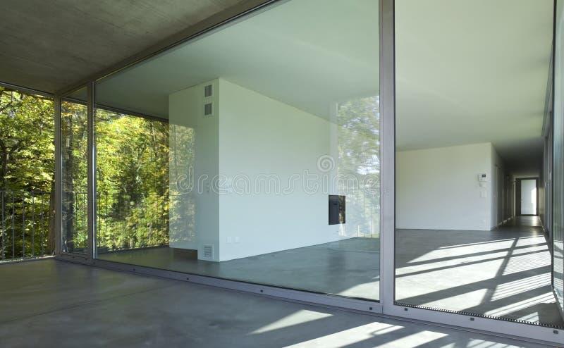 Interior de un cuarto vacío, una sala de estar Una pared blanca grande con una chimenea en el centro foto de archivo