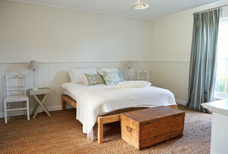 Interior de un dormitorio cómodo en un hogar del estilo rural imagen de archivo