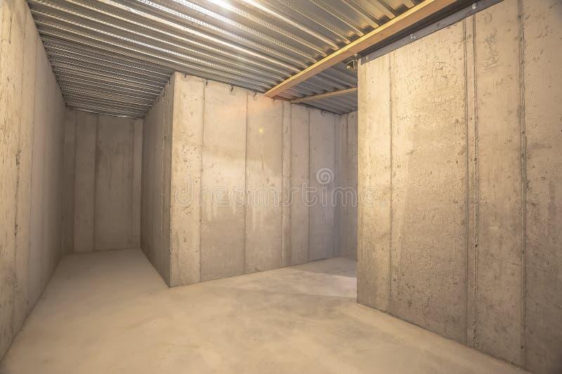Interior de un edificio vacío con el muro de cemento y el tejado acanalado del metal imágenes de archivo libres de regalías