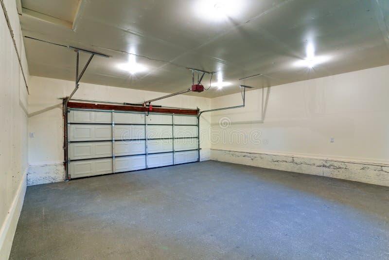 Interior de un garaje limpio vacío con a puerta cerrada imagenes de archivo