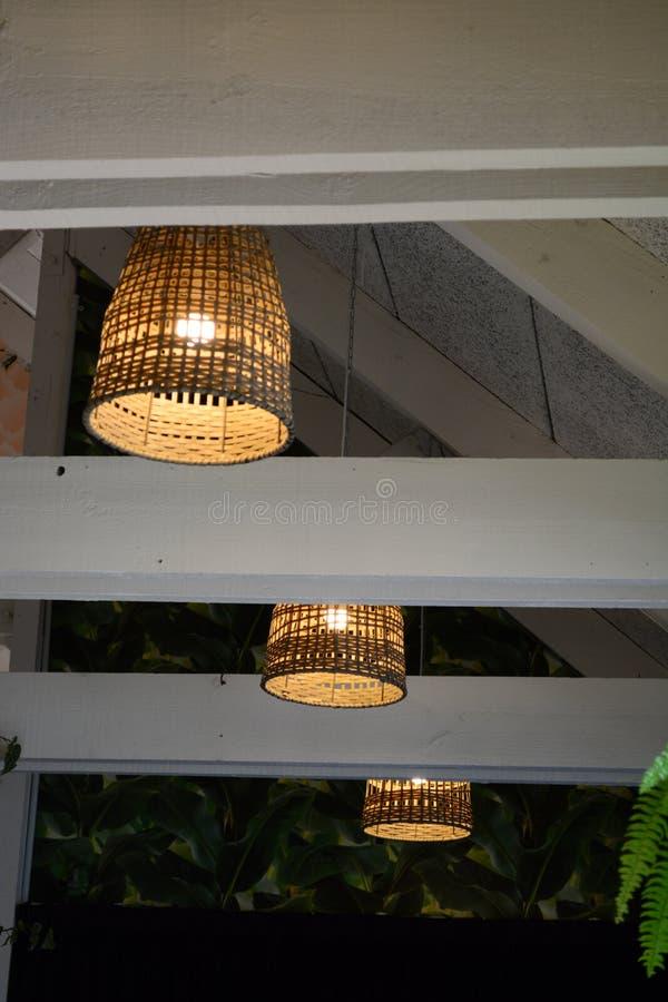 Interior de un restaurante pasado de moda precioso, con las lámparas colgando del alto techo; sombras de lámpara de mimbre viejas imagenes de archivo