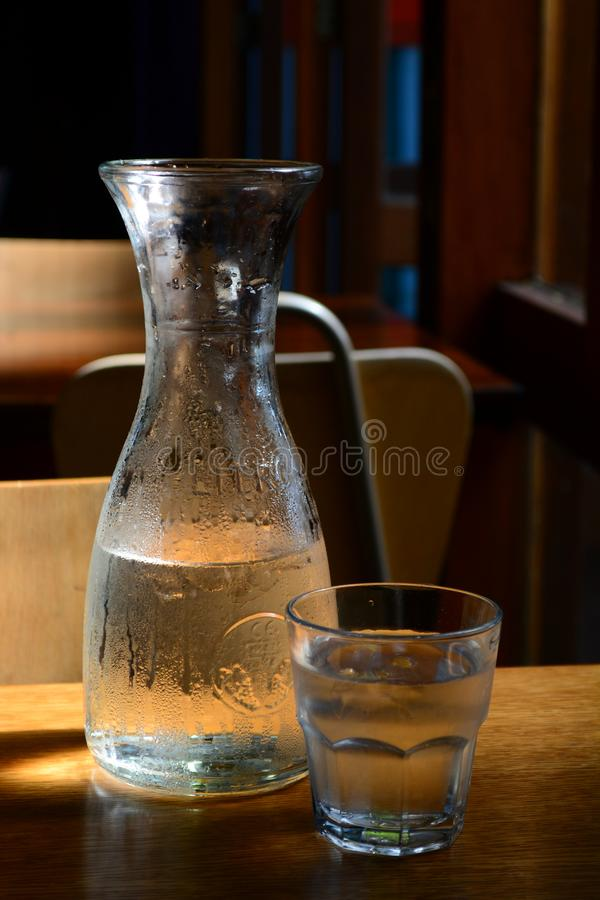 Interior de un restaurante pasado de moda precioso; un tarro y un vidrio de agua fría que esperan en una tabla foto de archivo