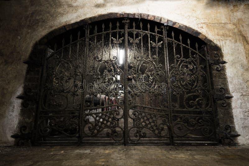 Interior de una bodega vieja, una puerta forjada del hierro foto de archivo