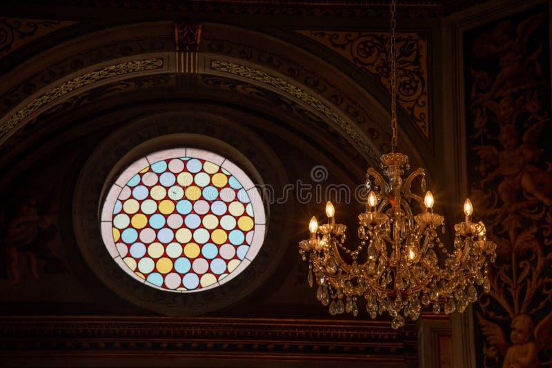 Interior de una iglesia con la ventana color de rosa en la lámpara de cristal y cristalina imagenes de archivo