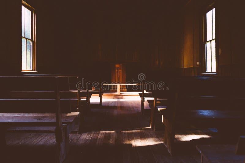 Interior de una iglesia cristiana de madera oscura con una cruz en el soporte en el campo fotos de archivo