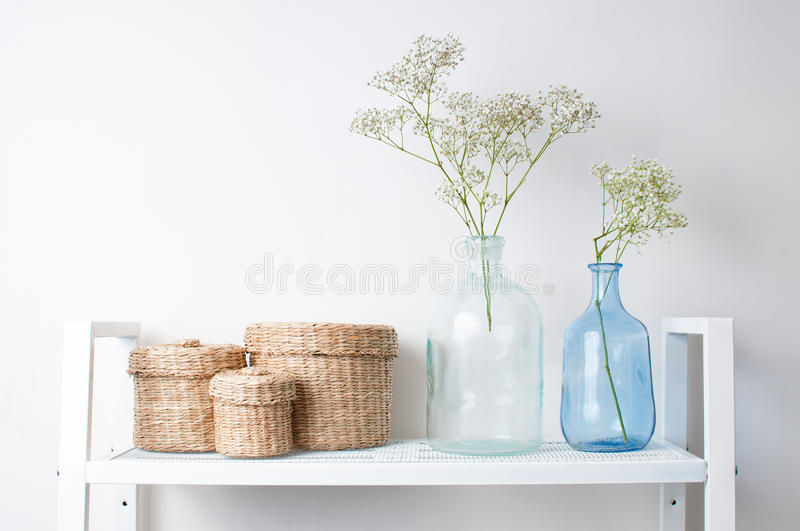 Interior decoration: branches in bottles and baskets. Home interior decoration: the branches in vintage bottles and baskets on white shelves