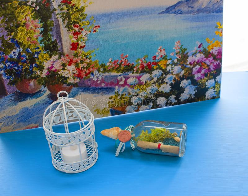 Interior decoration of a house, flowers, candles, birdcage on white and blue background. Still life natural with sea bottle and stock image