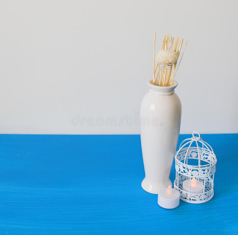 Interior decoration of a house, flowers, candles, vase, birdcage on white and blue background. Still life natural.  stock photos