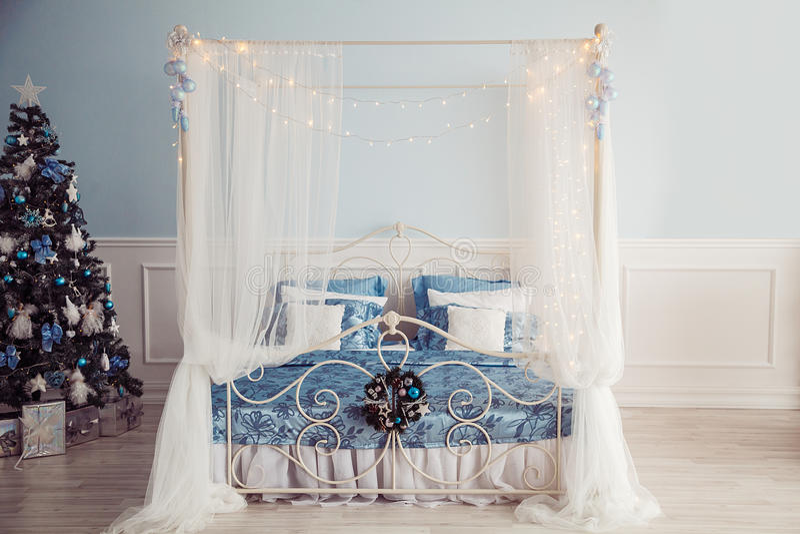 Interior del Año Nuevo con la cama y el árbol de navidad De azul y blanco fotos de archivo libres de regalías