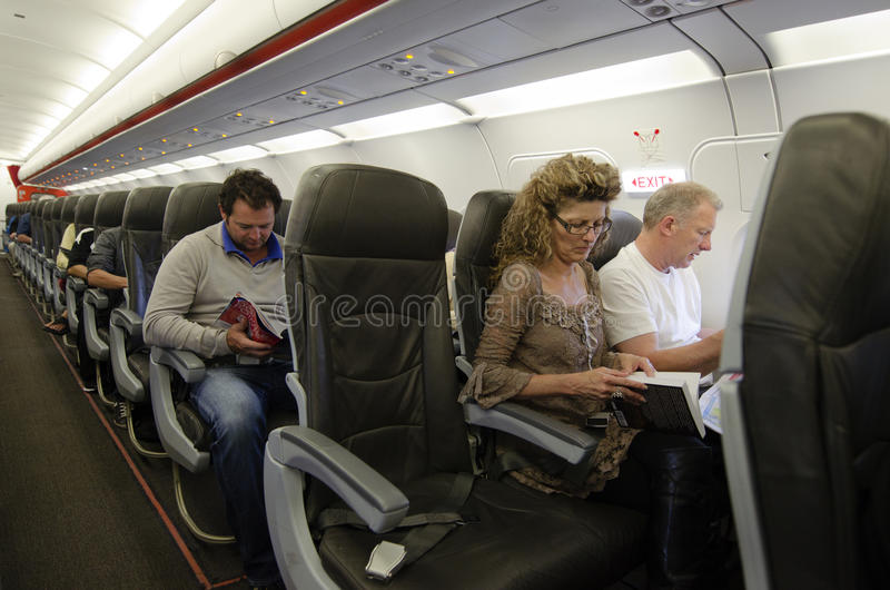 Interior del aeroplano con los pasajeros fotografía de archivo