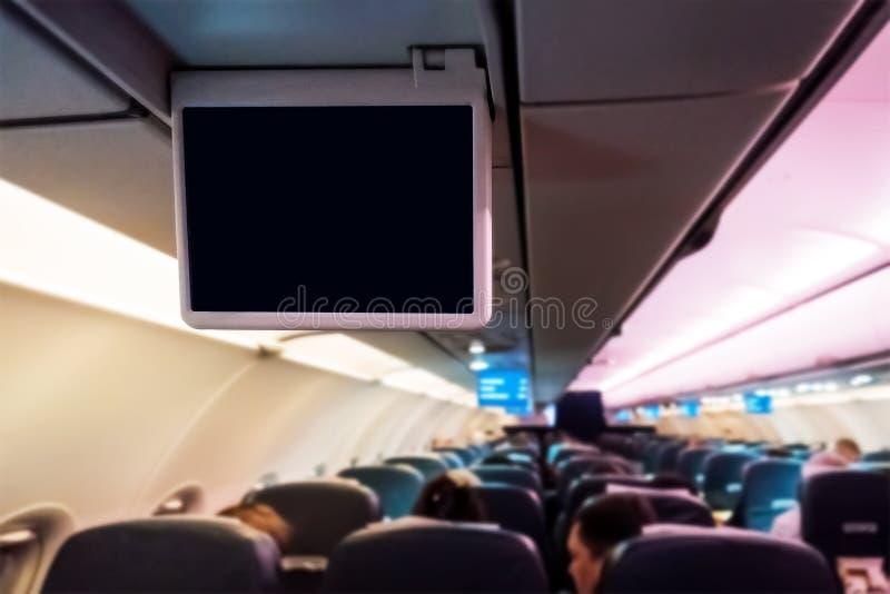 Interior del aeroplano del pasajero y de las pantallas en blanco del entretenimiento foto de archivo