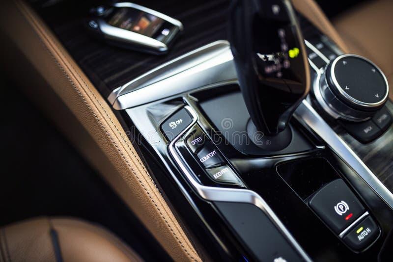 Interior del coche: Detalles de la consola central moderna con el botón de los diales, de los botones y del engranaje fotografía de archivo libre de regalías