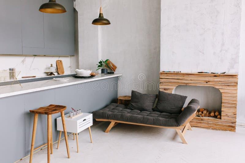 Interior del cocina-estudio moderno del desván en el apartamento Sitio, muebles, sofá cerca de la chimenea de madera imagenes de archivo