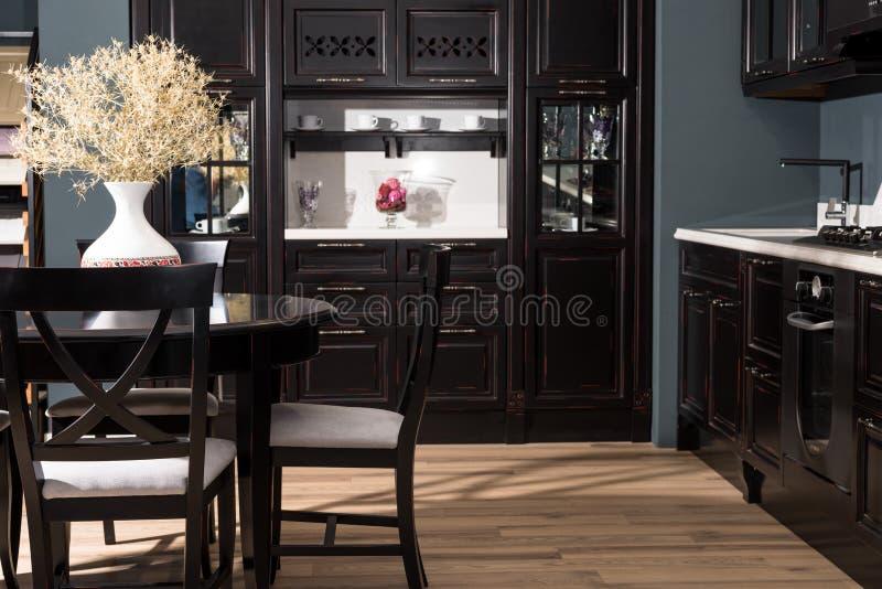 interior del comedor moderno con muebles y el florero negros de flores secadas foto de archivo