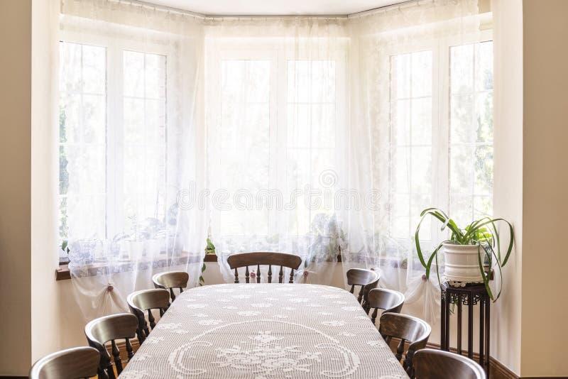 Interior del comedor del viejo estilo con una ventana grande adornada con fotos de archivo