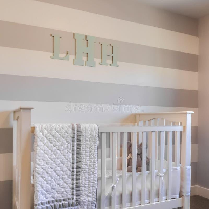 Interior del cuadrado de un cuarto de niños con las letras blancas del pesebre y del monograma en la pared rayada imagen de archivo libre de regalías