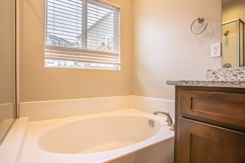 Interior del cuarto de baño con la bañera oval contra la pared y la ventana blancas con las persianas foto de archivo