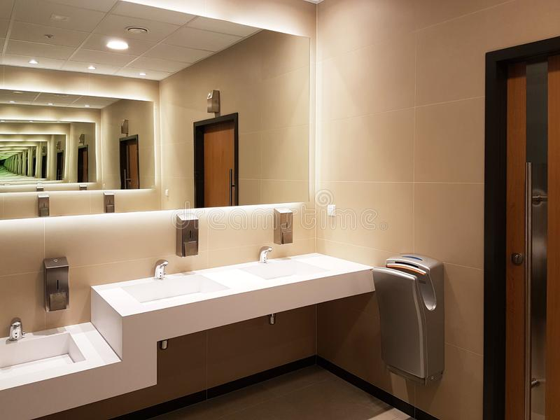 Interior del cuarto de baño en colores beige y blancos ligeros Lavabos de cerámica redondos Espejos, jabonera plástica y grifos d imagen de archivo libre de regalías