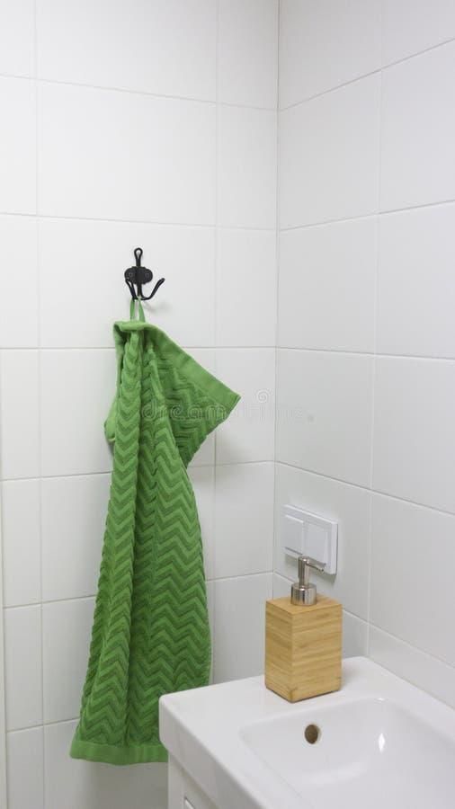 Interior del cuarto de baño en colores claros con el fregadero, el dispensador de bambú del jabón y la toalla verde imágenes de archivo libres de regalías