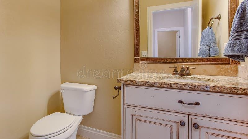 Interior del cuarto de baño del marco del panorama con vista de un retrete adyacente al área de la vanidad fotos de archivo libres de regalías