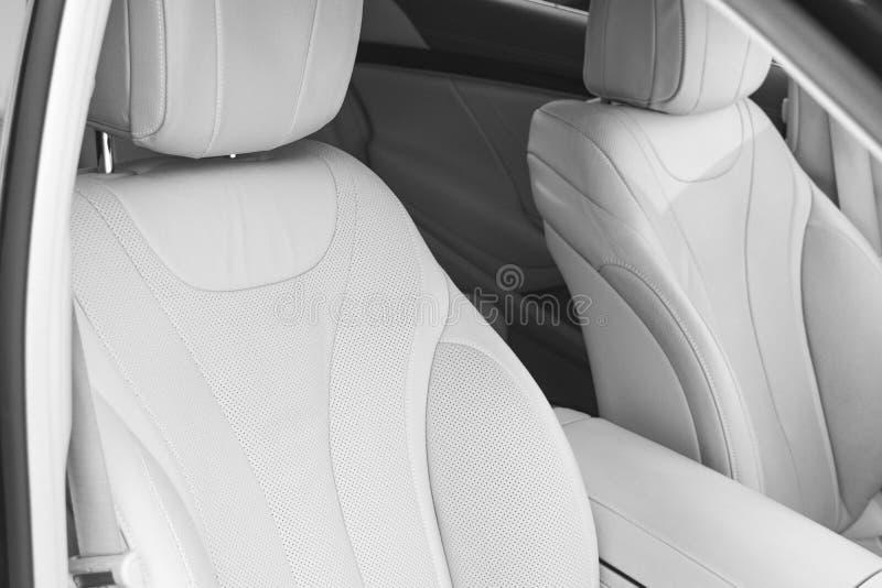 Interior del cuero blanco del coche moderno de lujo Asientos y multimedias blancos cómodos de cuero decorati exclusivo de madera  fotos de archivo