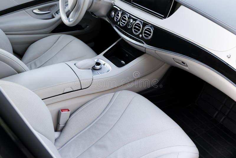 Interior del cuero blanco del coche moderno de lujo Asientos y multimedias blancos cómodos de cuero volante y tablero de instrume fotografía de archivo