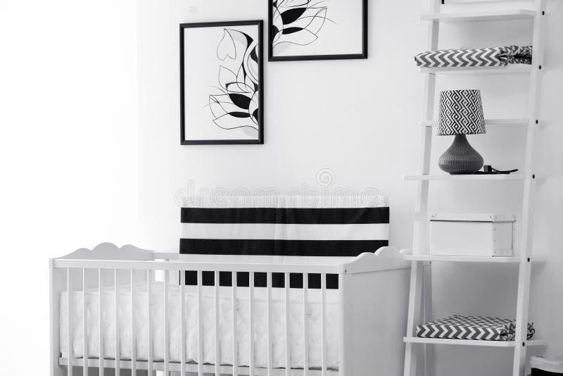 Interior del dormitorio del bebé con el pesebre y la decoración hermosa foto de archivo