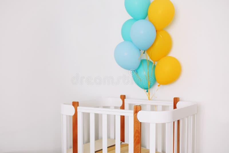 Interior del dormitorio del beb? Interior del sitio del bebé de Minimalistic Globos festivos delante de la cama de bebé Concepto  fotos de archivo