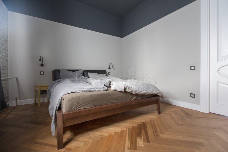 Interior del dormitorio con la cama sin hacer foto de archivo libre de regalías