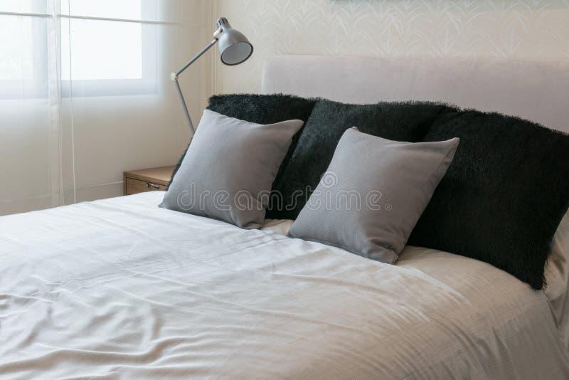 Interior del dormitorio con las almohadas grises en la cama blanca imagenes de archivo