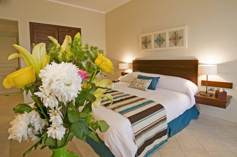 Interior del dormitorio con las flores imagen de archivo libre de regalías