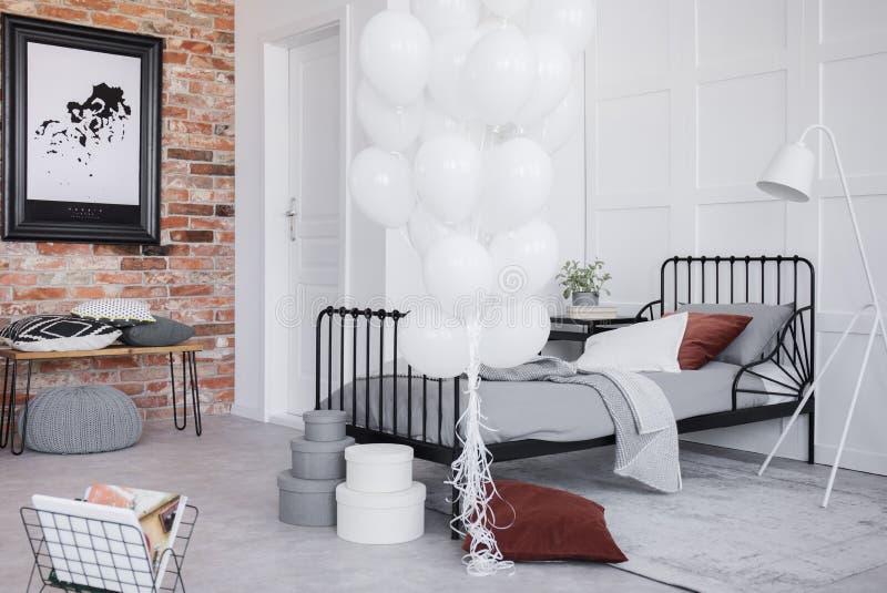 Interior del dormitorio con lecho gris, manojo de globos blancos y marco negro en la pared de ladrillo, foto real imagen de archivo