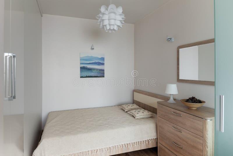 Interior del dormitorio en el pequeño apartamento moderno en estilo escandinavo foto de archivo