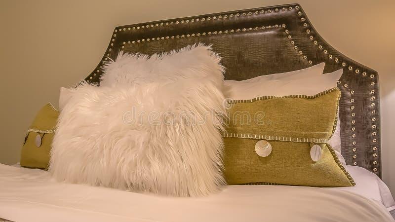 Interior del dormitorio del marco del panorama con las almohadas contra el cabecero tapizado del belgrave de una cama fotos de archivo libres de regalías