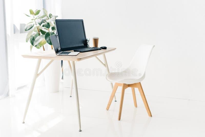 interior del lugar de trabajo con la silla, ordenador portátil, ordenador, taza de café de papel fotografía de archivo
