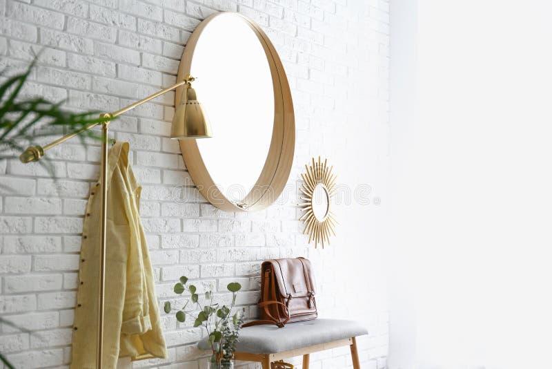 Interior del sitio con el espejo redondo que cuelga en la pared de ladrillo imagen de archivo