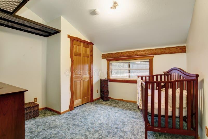 Interior del sitio del cuarto de niños con el pesebre del bebé en casa de la cabaña de madera imagen de archivo