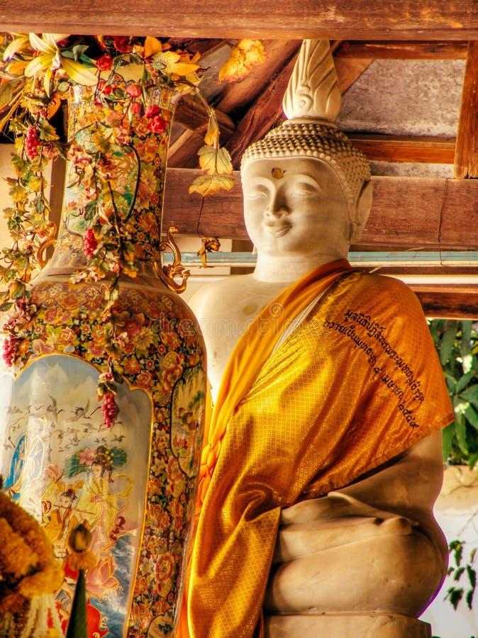 Interior del templo situado en Ayutthaya Tailandia, una estatua de Buda y florero largo con las flores imágenes de archivo libres de regalías